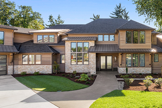 Luxury home exterior on sunny day with blue sky. Features three car garage, large driveway, and elegant design
